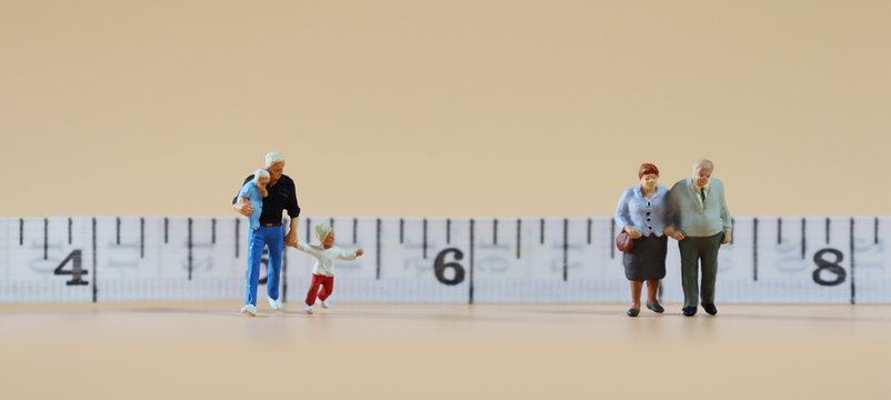 The miniature people standing in front of the tape measure. The concept of social distance.
