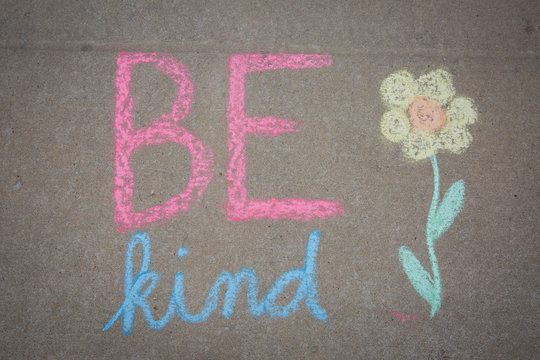 Be Kind words and a flower drawn with sidewalk chalk - temporary art