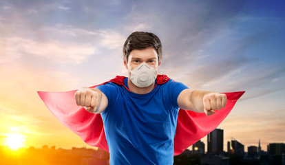 health, safety and pandemic concept - young man in red superhero cape wearing face protective mask or respirator for protection from virus disease flying over city sunset on background