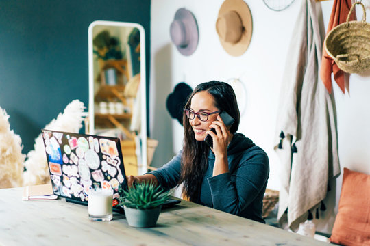 Young charming stylish woman in a home office sits at a desk, looks at a laptop and speaks while smiling on the phone. The concept of freelance and remote work. Stay safe and self-isolation.