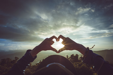 Woman making heart with her hands on sunset