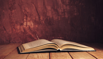 Beautiful ancient open old book on a red  wooden table and dark-red wall background behind. Wall mural