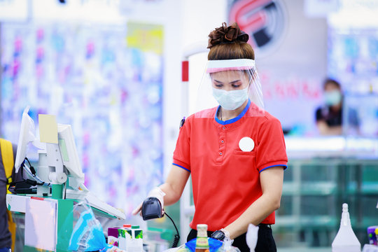 female supermarket cashier in medical protective mask and face shield working at supermarket
