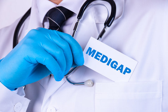 Doctor, man put a card with the text MEDIGAP in his pocket. Medical concept.
