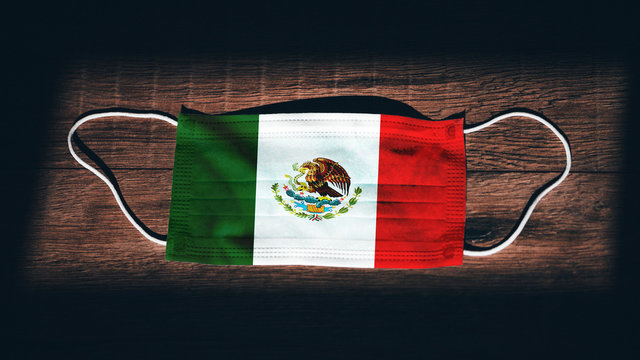 Mexico National Flag at medical, surgical, protection mask on black wooden background. Coronavirus Covid–19, Prevent infection, illness or flu. State of Emergency, Lockdown