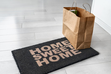Home delivery of food grocery bag left at door entrance mat for Corona virus prevention safety. Precaution measures against COVID-19, paper shopping bag delivered without contact.