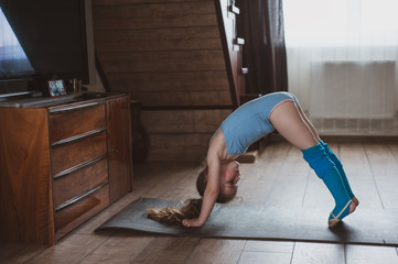 The girl does gymnastics at home. Gymnastics video tutorial. Gymnastic exercises. The idea for a children's activity in quarantine
