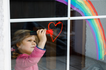Adoralbe little toddler girl with rainbow painted with colorful window color during pandemic coronavirus quarantine. Child painting rainbows around the world with the words Let's all be well. Fototapete