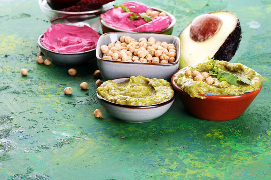 A variety of colored hummus, beetroot hummus, hummus with avocado on background. Veggie Clean eating, dieting, vegetarian party food.