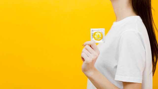 Side view woman holding a condom with copy space