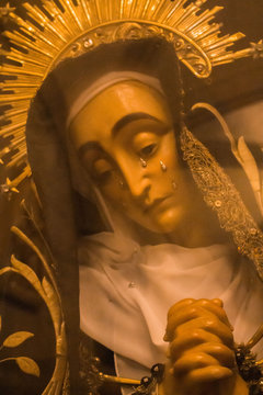 Portugalete, Spain - 10/17/2019: statue of Virgin Maria with tears through glass. Sculpture of Saint Maria with tears behind glass. Sadness and grief concept. Sad Madonna face. Pray and faith concept.