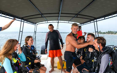 group of divers from diving center on a boat swim to the dive site, young boys and girls, an adult instructor, Asia Sri Lanka. Wall mural
