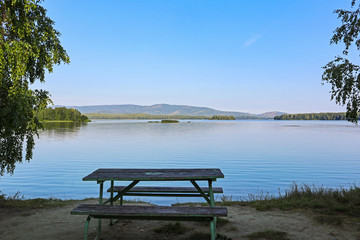 Wall Mural - Lake shore and empty picnic bench. Summer landscape of a lake or river with calm water and a park furniture to relax near the lakeside. Beautiful and tranquility view of Sungul lake in Russia.