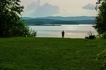 Wall Mural - Lake shore and silhouette of the fisherman. Summer landscape of a lake or river with calm water and one man on the lakeside. Vacation and relax on the Sungul lake in Russia. Tranquility scenic scenery