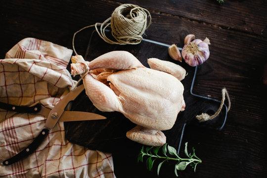 Raw whole chicken being prepared.