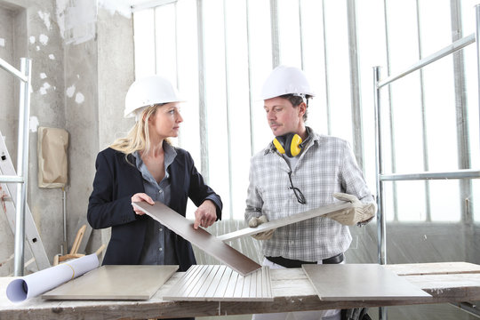 man and woman architect interior designer and foreman worker together with tiles samples and decorative materials discussing the project for interior decoration inside the construction building site