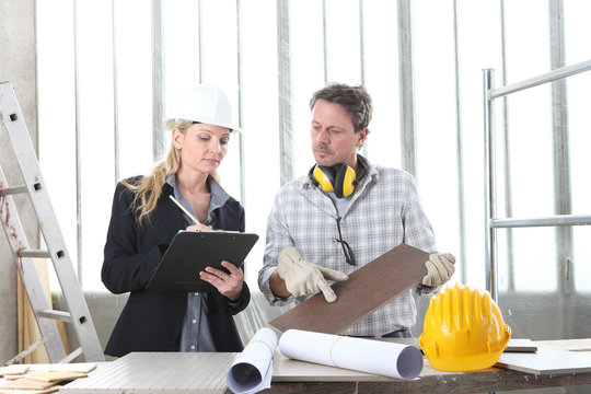 man and woman architect interior designer and foreman worker together with tiles samples and decorative materials discussing  project for interior decoration inside the construction building site