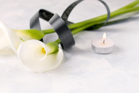 White Zantedesia flower tied with a black ribbon, next to a candle on a light background. Copy space. The concept of death, mourning Stock Photo | Adobe Stock