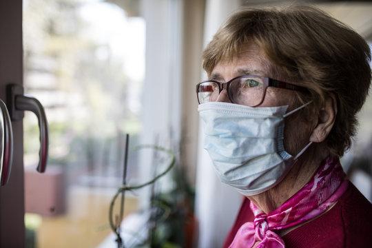 Seniorin mit Mundschutz schaut aus dem Fenster