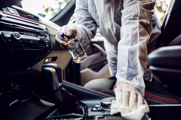 Man in protective suit with mask disinfecting inside car, wipe clean surfaces that are frequently touched, prevent infection of Covid-19 virus coronavirus,contamination of germs or bacteria.  Fototapete