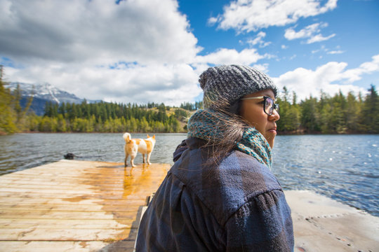 Woman sitting on a dock with her dog a lake below Curry peak in Pemberton, British Columbia, Canada.