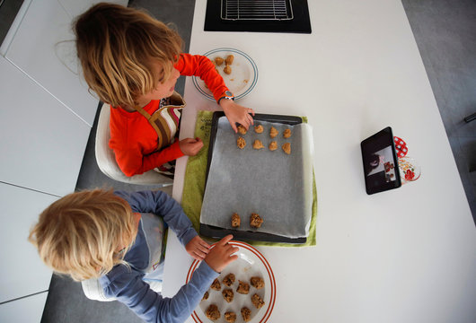 Children make cookies following the instructions of their grandparents during the coronavirus disease (COVID-19) outbreak, in El Masnou