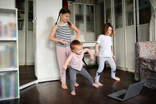 Three children dancing in video chat online