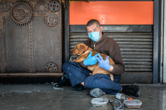Hungry sick homeless beggar man on the street with his dog begging for money and food to eat wearing the medicine mask and gloves to protect himself from coronavirus or covid 19 during the pandemic