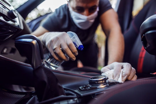 Man in protective suit with mask disinfecting inside car, wipe clean surfaces that are frequently touched, prevent infection of -covid 19 virus ,contamination of germs or bacteria. Infection.