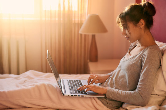 concentrated successful female freelancer typing on laptop keyboard while sitting on bed. Brunette girl in pajamas working from home, remote work, internet business, sunlight from window on background