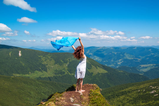 Young woman in white summer dress stands on a rock and looks into the valley, in her hands develops a lightweight blue scarf