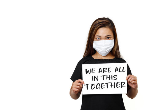 Asian lady standing with we are all in this together text front view in white plain background. Young lady looking straight wearing face mask for protection against coronavirus.