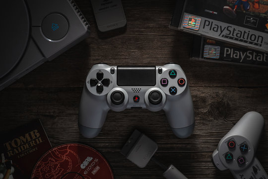 Odessa, Ukraine - December 7, 2019: The DualShock4 Wireless Controller for PlayStation4. Gamepad gray for PS4 on a vintage wooden table among the PS1 console and games.