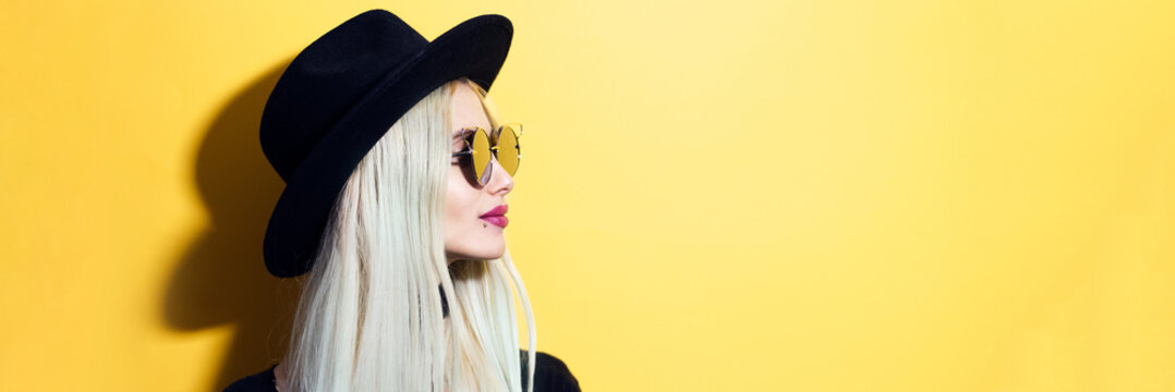 Panoramic profile portrait of young teenage blonde girl wearing sunglasses and black hat on background of pastel yellow color with copy space.