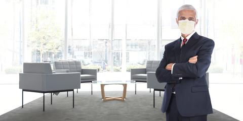 Businessman standing in empty office without customers or employees wearing his COVID-19 mask practicing social distancing.