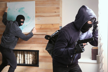 Dangerous masked criminals stealing picture from house