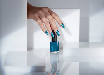 Close up of woman's hand holding blue nail polish bottle