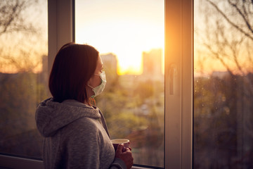 Woman near window at sunset in isolation at home for virus outbreak. Stay home concept