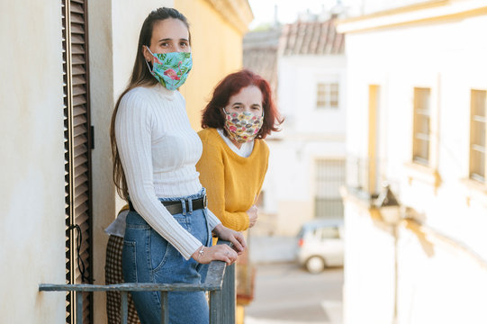 Two women with protective masks in balcony