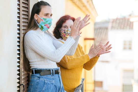 Two women with face mask clapping on the balcony