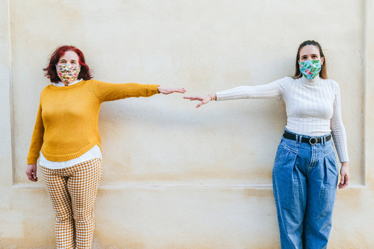 Two women with face masks representing social distancing