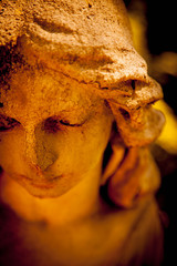 Wall Mural - Beautiful sad angel. Fragment of ancient stone statue. Selective focus on eye.