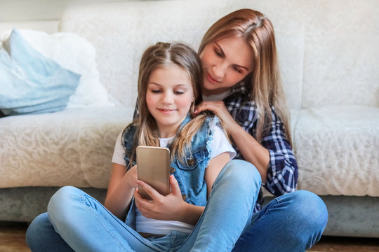 mom and daughter are sitting on the couch at home with the phone