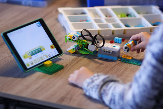 Kyiv, Ukraine - December 1, 2018: Closeup of boy's hands constructing Lego WeDo robot and programming it at robotics lesson at school