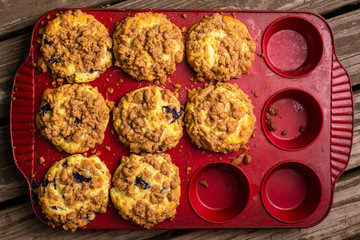 Freshly baked blueberry crumb muffins in baking tray