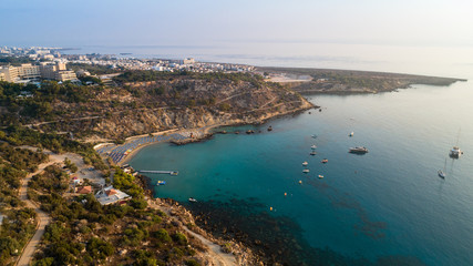 Aerial bird's eye view of Konnos beach, Cavo Greco Protaras, Paralimni, Famagusta, Cyprus. Famous tourist attraction golden sandy bay with boats, yachts in the sea, sunbeds, water sports, from above.