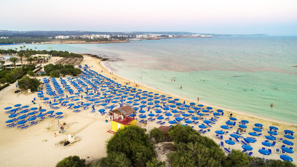 Aerial bird's eye view of famous Makronissos beach coastline, Ayia Napa, Famagusta, Cyprus. Landmark sea tourist attraction Makronisos bay at sunset with golden sand, sunbeds in Agia Napa from above.