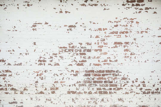 A whitewashed old painted vintage brick wall of a home commercial building perfect for a backdrop, web banner or background for design with lots of copy space