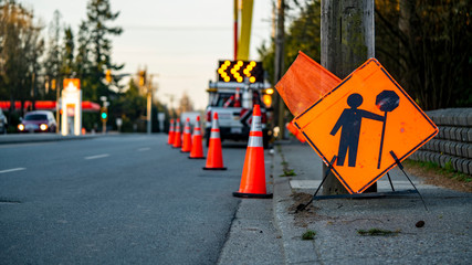 Lane closure on a busy road due to maintenance signs detour traffic temporary street work orange lighted arrow, barrels and cones.