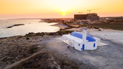 Aerial bird's eye view of coastline sunset, traditional landmark white and blue chapel at Agia Thekla beach, Ayia Napa, Famagusta, Cyprus from above.Tourist attraction golden sand bay, church, sunbeds